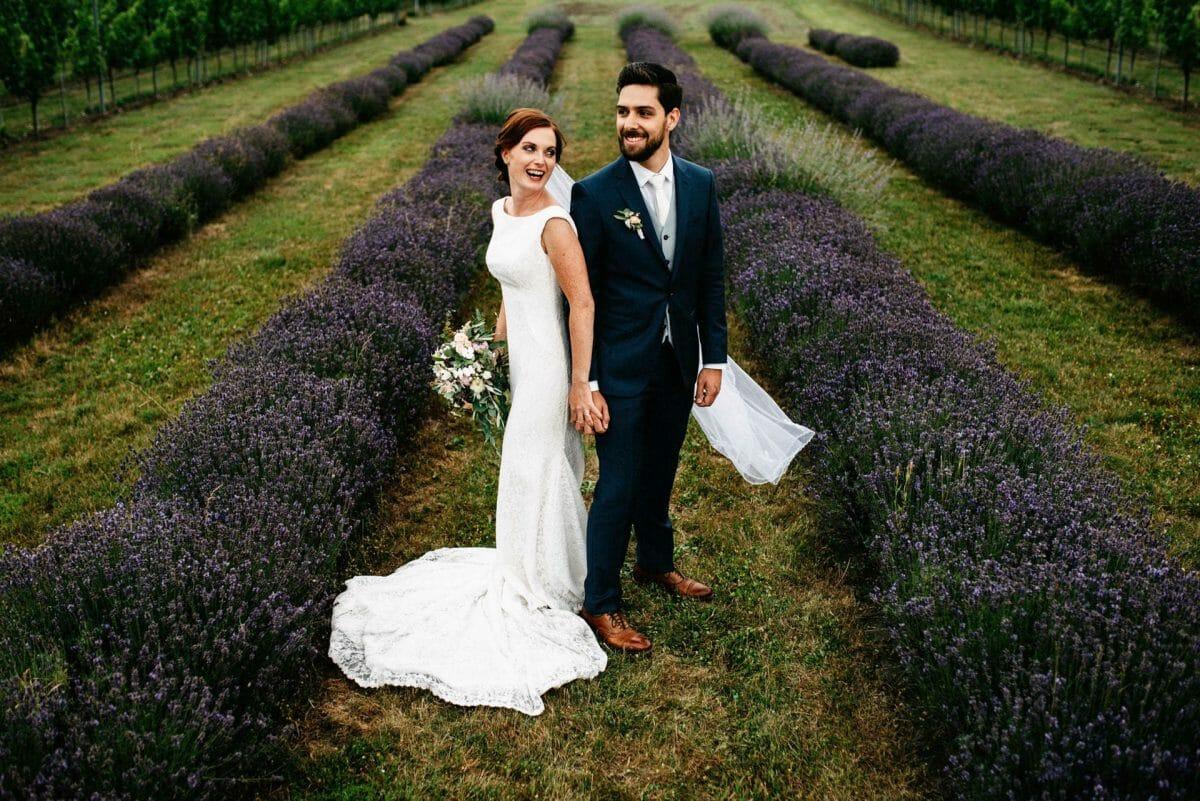 Hochzeitspaar steht im Lavendelfeld in der Steiermark und sieht sich verliebt an. Braut hat Brautstrauß in der Hand.
