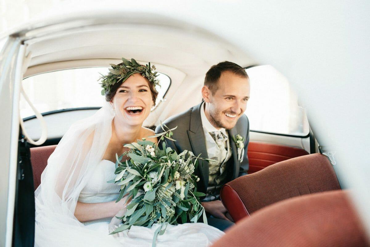 Brautpaar sitzt in altem VW Käfer und lacht laut vor lauter Freude über die Hochzeit