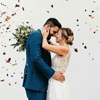 Glücklicher Moment zwischen Brautpaar während Blumen auf sie fliegen