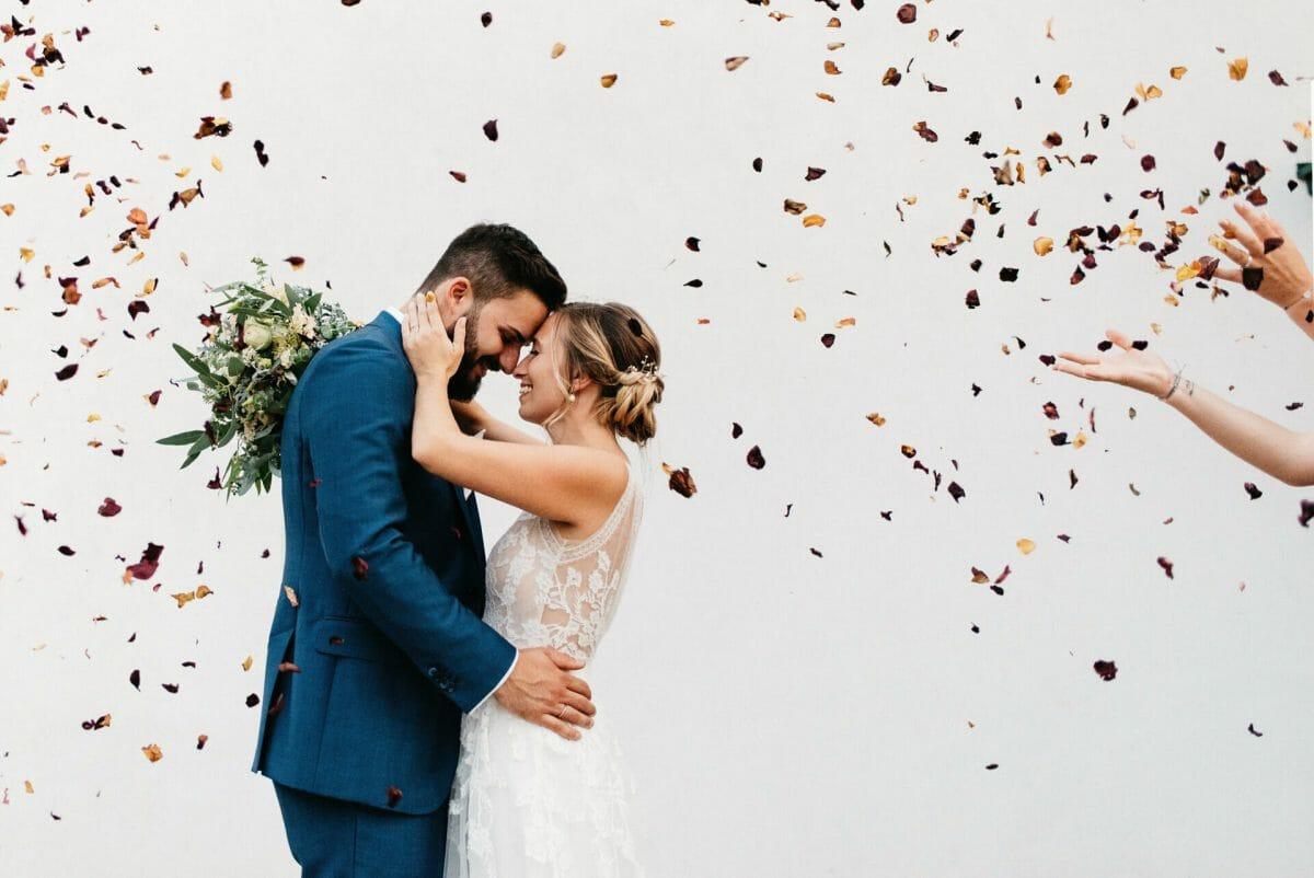 Rosenblätter fliegen über das Brautpaar und man sieht Hände die sie werfen